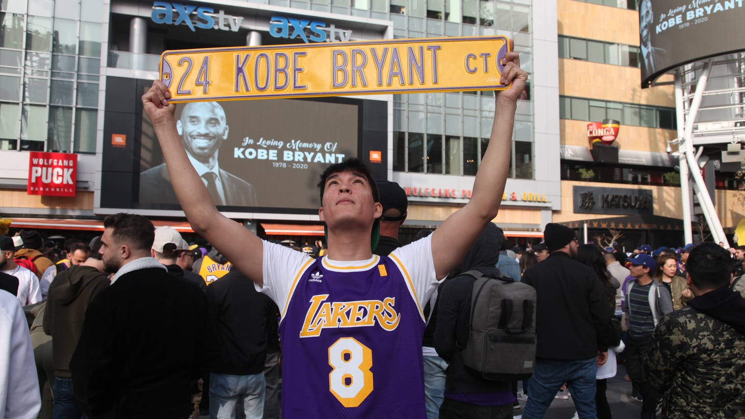 Sergio Carrillo holds a Kobe Bryant street sign.