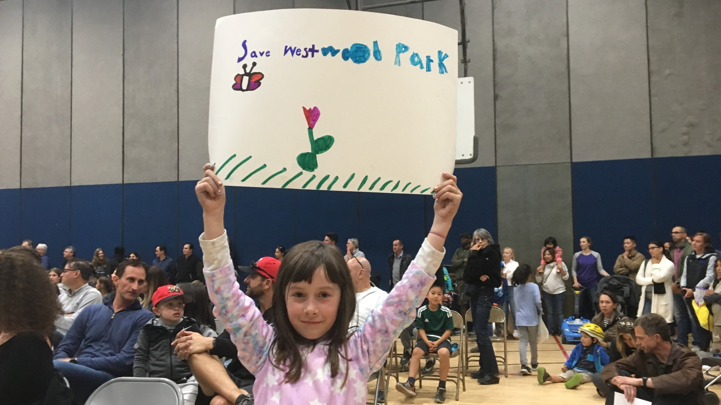 A young girl holds up a sign protesting the proposed synthetic grass field at a meeting at Westwood Recreation Center on May 23.