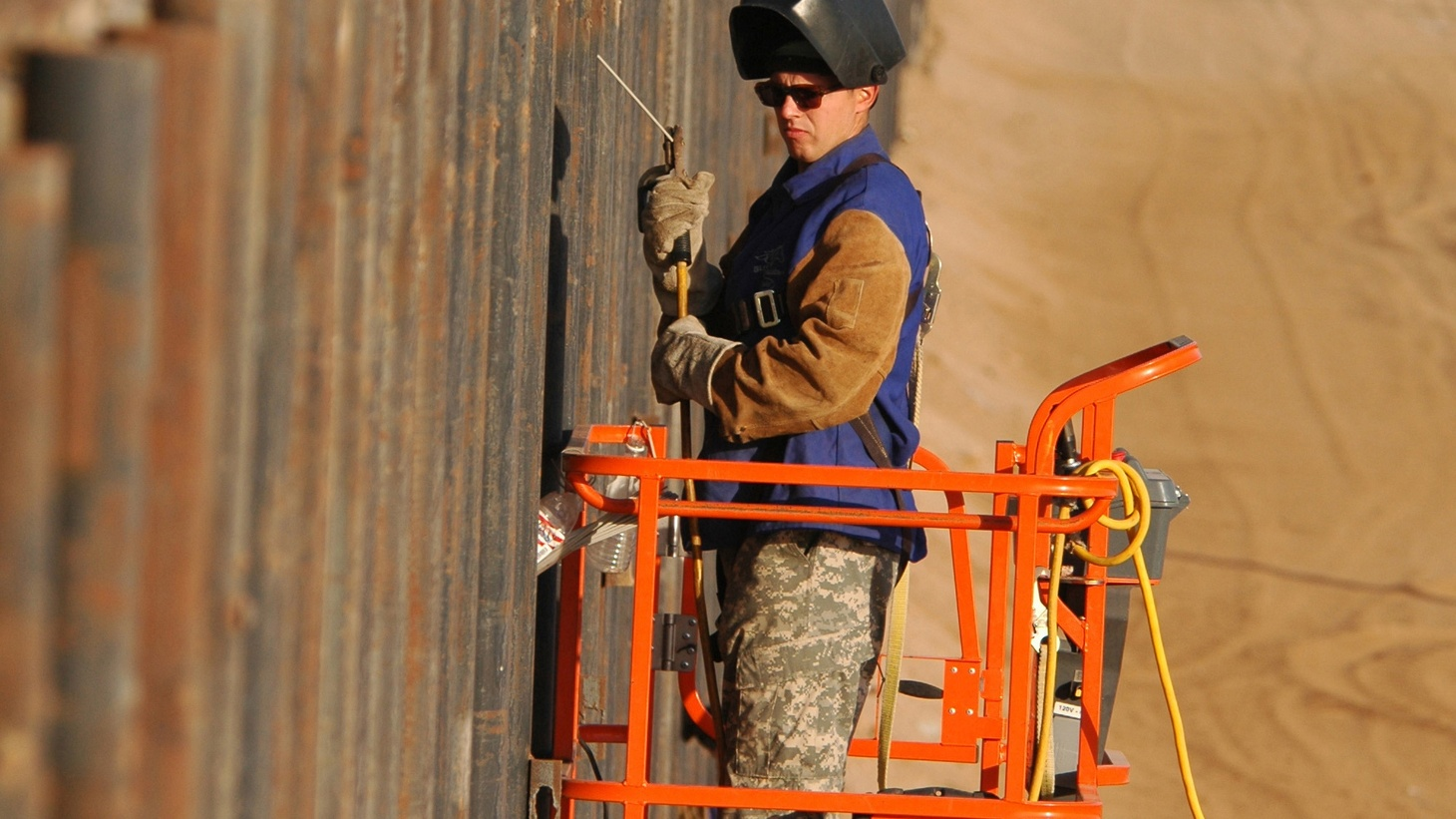US Army Spc. Michael J. Westall uses a motorized boom lift to get into  position to weld the reinforcement of the primary steel border fence  along the United States-Mexico border on June 7, 2007.  Photo by Senior Master Sgt. David H.