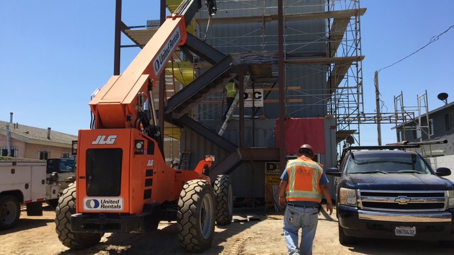 Workers construct an affordable project out of shipping containers for FlyawayHomes in South LA.