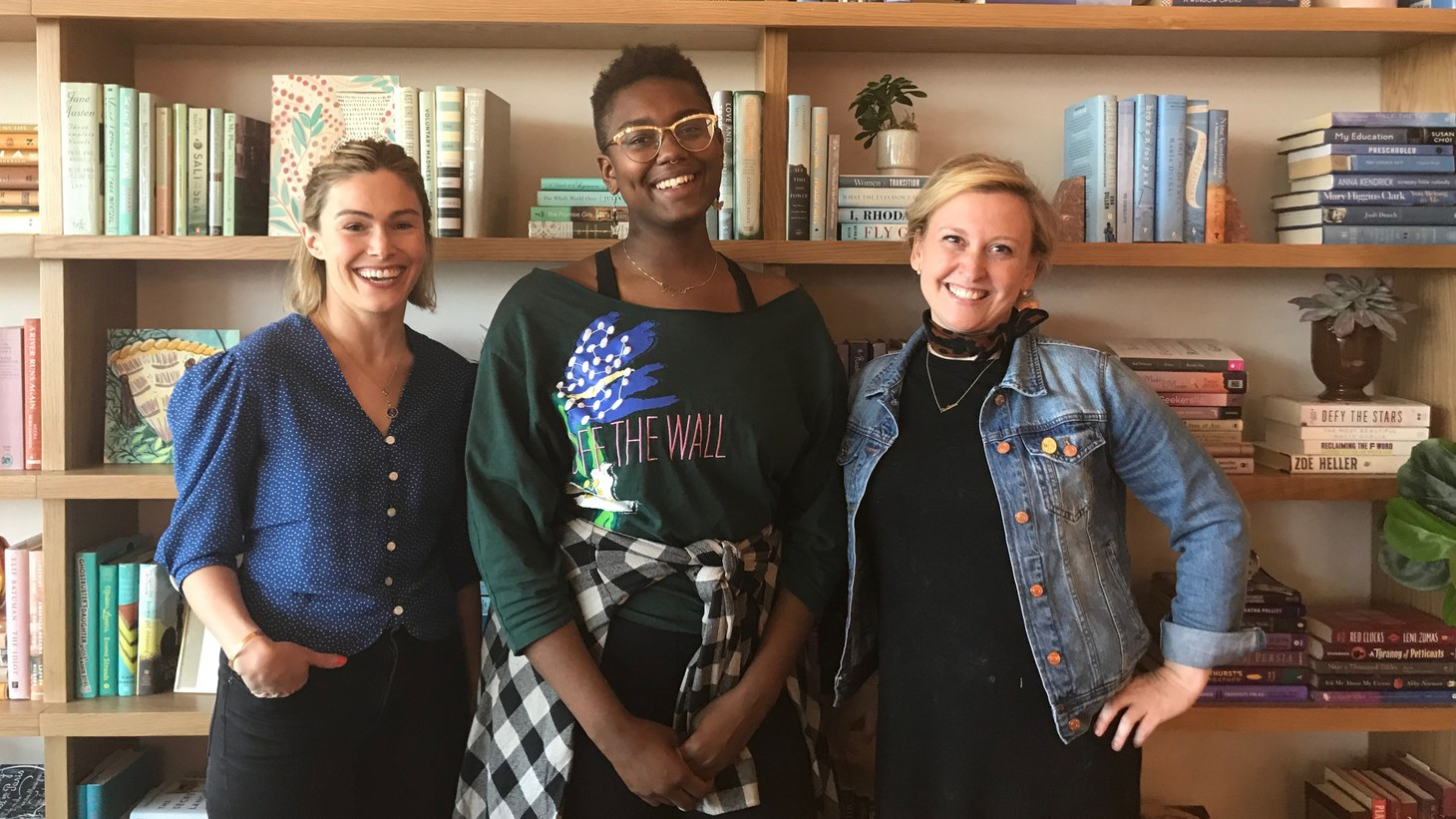 From left to right: The Wing members Meredith Russo, Royal Scales and Jessica Goldklang in front of the lending library sorted by color.