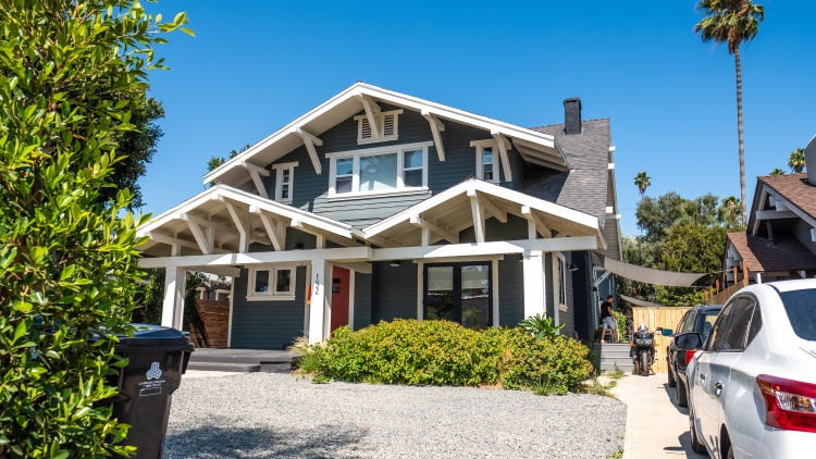 A large two-story Craftsman house on a residential street in Koreatown has been subdivided into 15 single-occupancy bedrooms and bathrooms, and common living and dining areas.