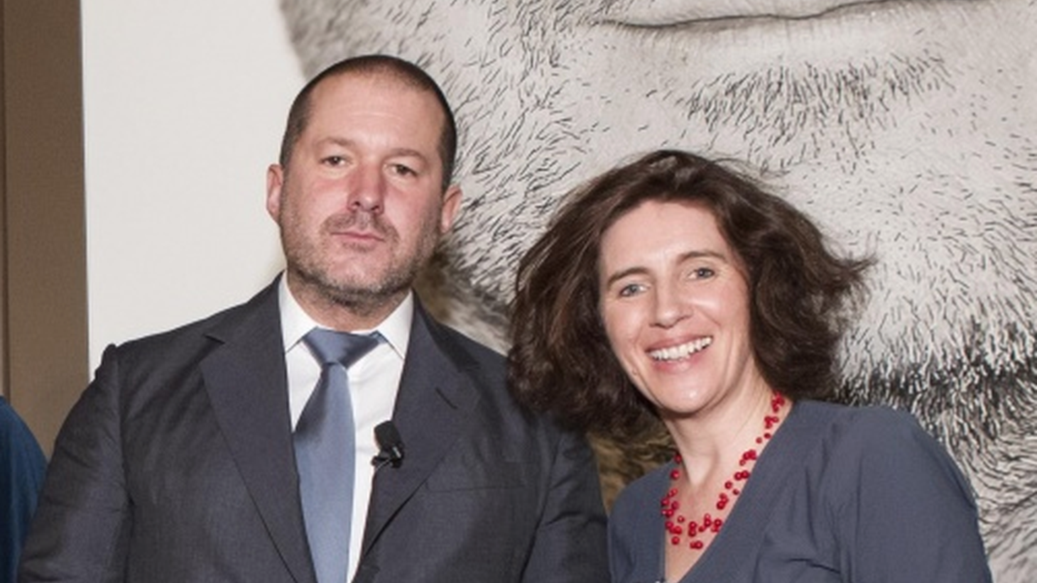 DnA's Frances Anderton, right, stands with her stunningly successful countryman Sir Jony Ive, under a blow-up photo of the designer at an SF MOMA fundraiser. (October, 2014)