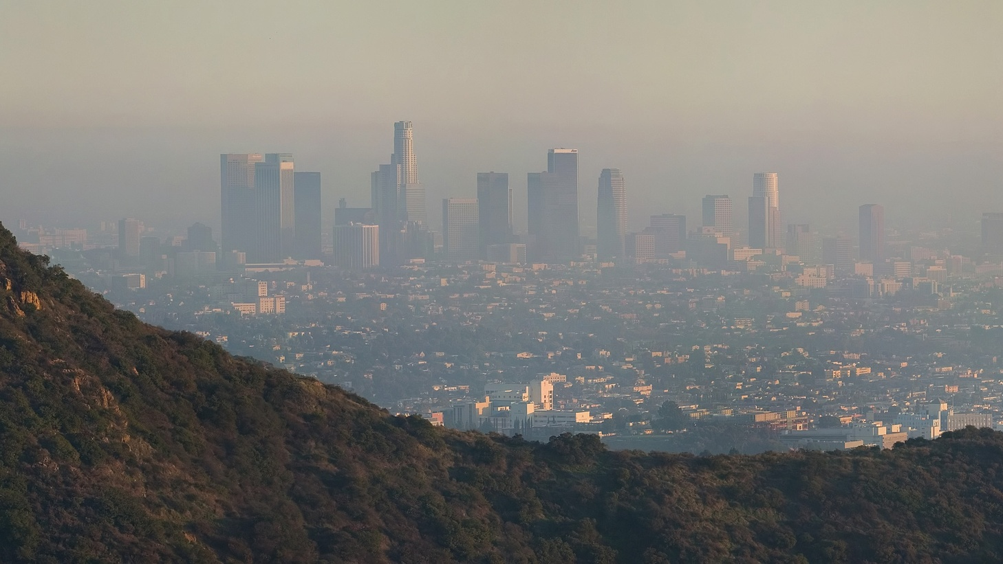 Looking down from the Hollywood Hills, with Griffith Observatory on the hill in the foreground, air pollution is visible in downtown Los Angeles on a late afternoon.