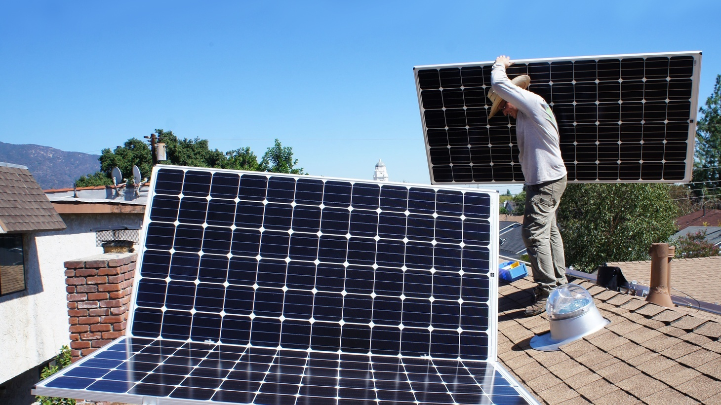 Workers install a residential solar power system at a home in Monrovia.