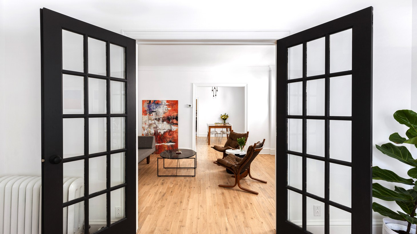 This Sweeten couple brought a minimalist vibe to their 1920s house in Midwood Brooklyn by adding molding, a graphic color scheme, and a set of French doors in the foyer for a dramatic entrance.