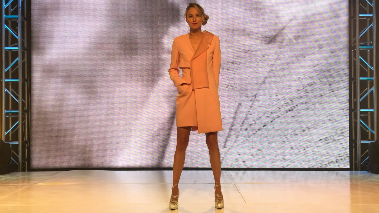 A model shows off the coral pink wool outfit with a silk lining designed by Oli Perez, a fashion student at Otis College of Art and Design. Perez's class worked with designer Jason Wu for nine months.