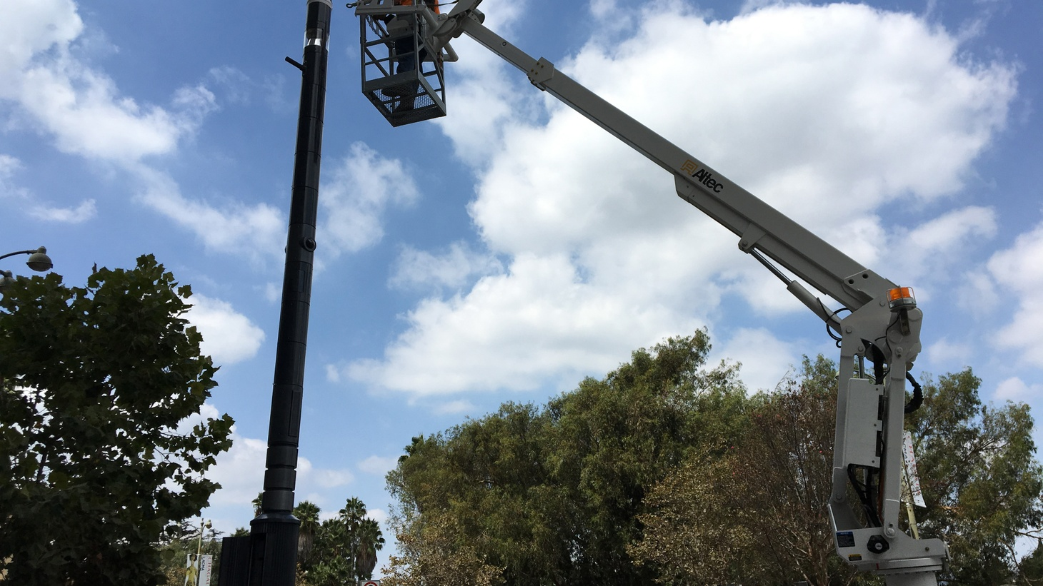 """Workers install a """"smart node"""" on Wilshire Boulevard. It's part of a pilot project led by the City of LA's Bureau of Street Services."""