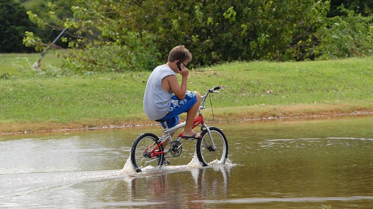Brandon Jernigan talks on a cell phone while riding his bike through flood waters.