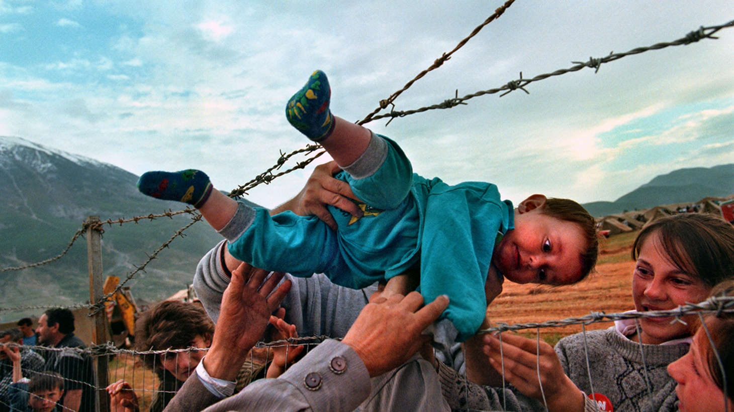 "Family members, reunited after fleeing Kosovo, pass 2-year-old Agim Shala through the barbed wire fence into the hands of his grandparents at a camp in Albania. On view as part of the exhibition ""W