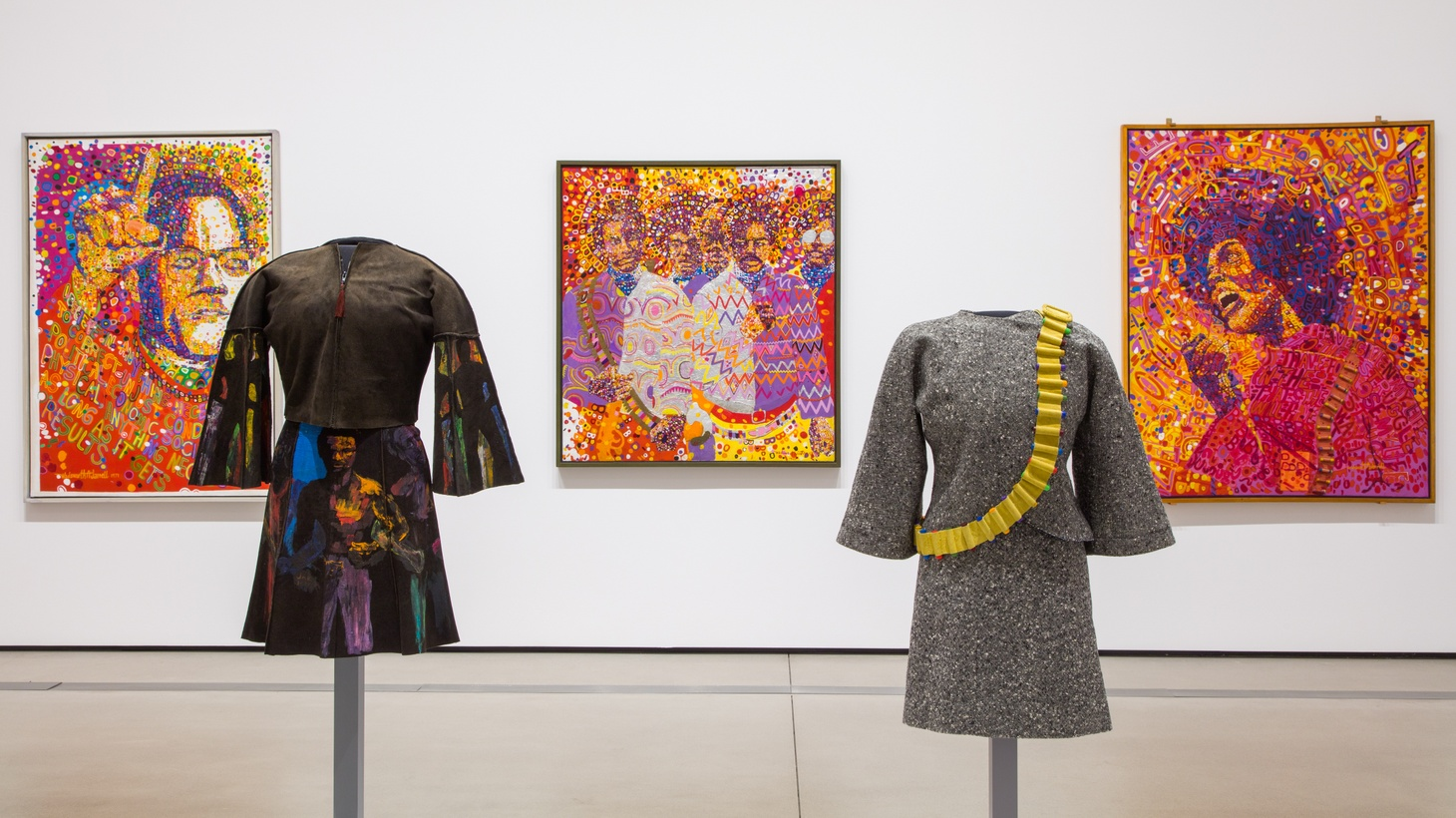 "Installation view of ""Soul of a Nation: Art in the Age of Black Power 1963-1983"" at the Broad, 2019, featuring paintings by Wadsworth Jarrell and dresses by Jae Jarrell."