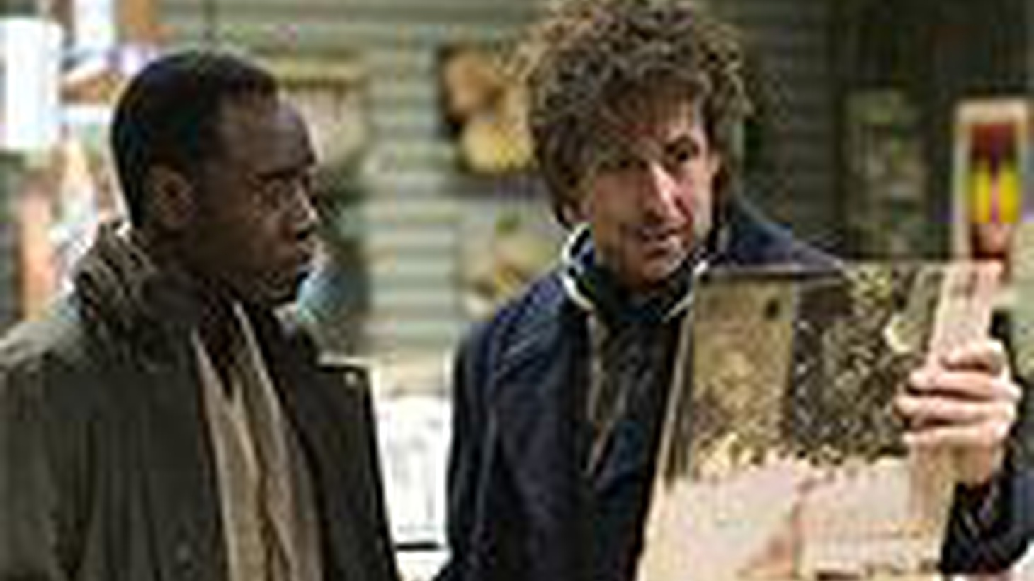"""In the opening scene of """"Reign Over Me,"""" we hear the strains of Graham Nash's """"Simple Man,"""" and see a spectral figure, head encased in huge headphones, buzzing through the streets of nighttime Manhattan on a scooter that looks like a motorized skateboard. The scooterist's name is Charlie Fineman, he's played by Adam Sandler, and he's anything but simple. Like many of Sandler's characters, Charlie boils with rage beneath a placid exterior. The difference here is the source of his distress – his wife and children were on one of the planes that hit the World Trade Center on 9/11, and losing them has turned Charlie, once a successful dentist, into a sort of Rain Man, shut off from the world."""
