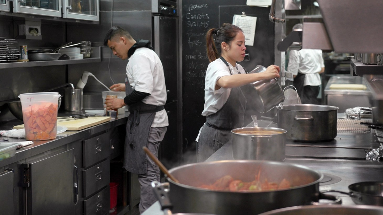 Cooks in your typical restaurant kitchen.