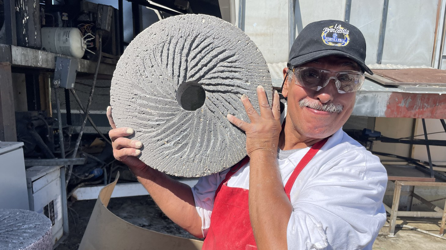 """Cesario """"Chayo"""" Covarrubias holding a millstone used to grind corn to make masa for tortillas. He's worked at La Princesita Tortilleria in East LA since 1988."""