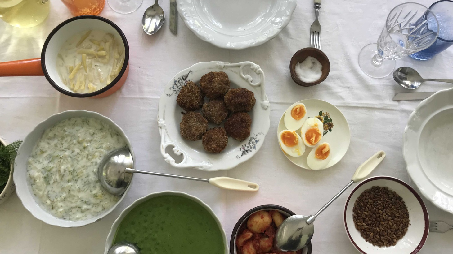 A Hungarian summer spread of zucchini, wax bean, and pea fözeléks, potatoes with tomato and tarragon, pork meatballs, and elderflower spritzer