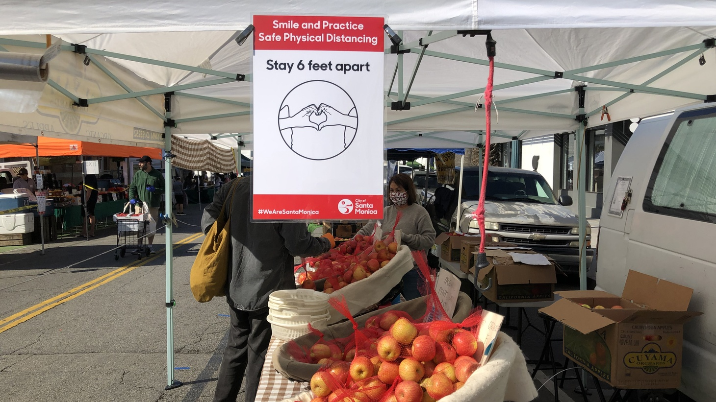 A sign at the Santa Monica Farmers Market reminds shoppers to stay six feet apart.