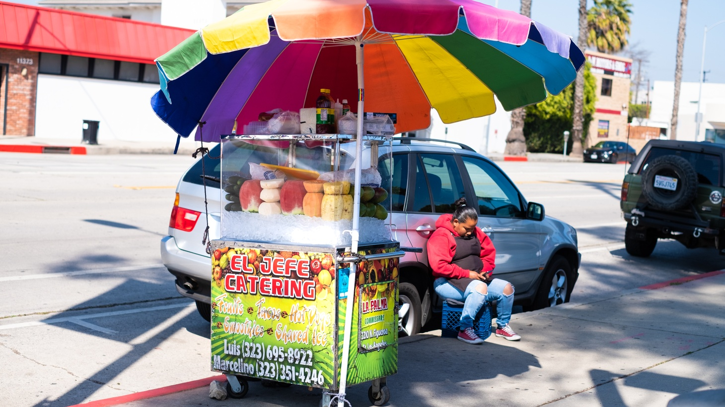 A woman waits for customers by her fruit stand in Culver City. Many fruteros start work within days of arriving in the United States.