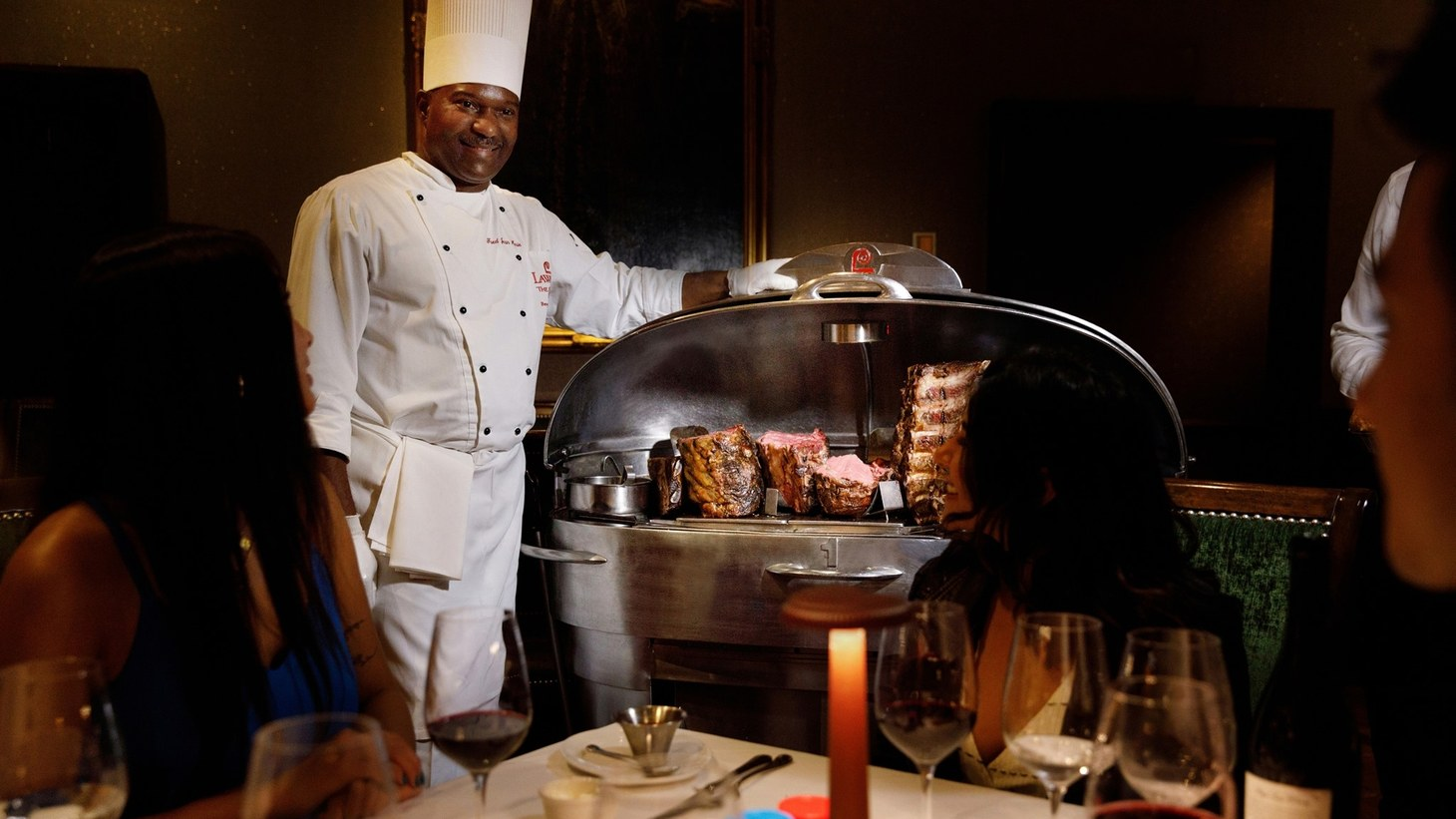Servers rolling stainless steel carts take six months to a year to earn a medal, signifying the completion of training to cut the perfect slice of prime rib at Lawry's.