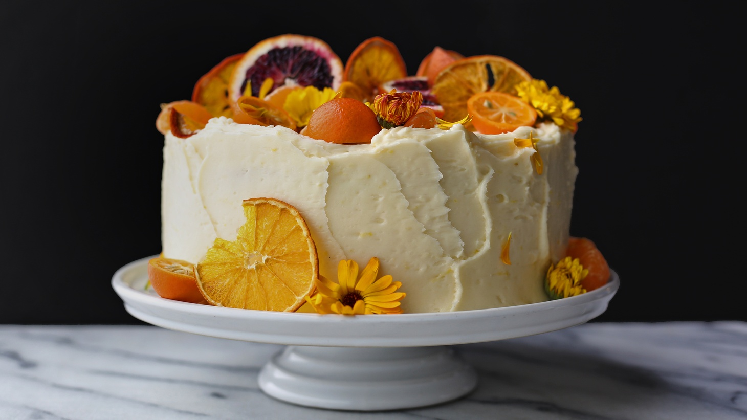 Lemon cake layered with tart lemon curd, covered in white chocolate buttercream. Topped with a bountiful arrangement of fresh seasonal flowers and citrus.