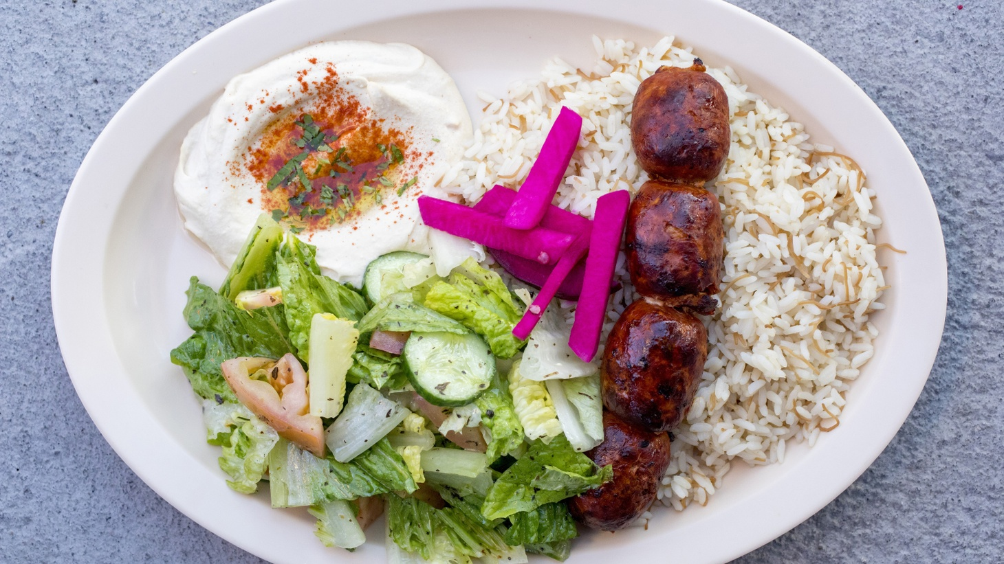 Los Angeles Times restaurant critic Patricia Escárcega reviews X'tiosu Kitchen in Boyle Heights. Pictured: chorizo kebab served with rice, Lebanese salad, and hummus.