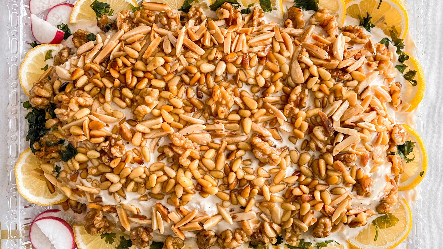Bill Addison discovers homestyle Lebanese food not typically found on restaurant menus at Mama Lina Cooks, including this samke harra — fish cloaked in tahini sauce with layers of cilantro and walnuts, and topped with pine nuts, slivered almonds, and more walnuts.