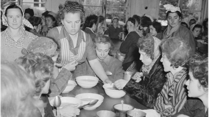 Women inmates enjoy a meal of hot soup in one of the huts. Bergen-belsen Concentration Camp, April 1945.