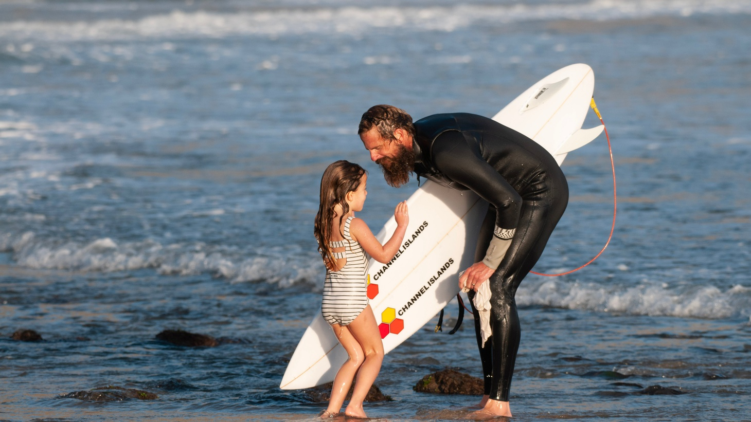 Surfer and former lead pastor of Reality Ministries Britt Merrick with his daughter.