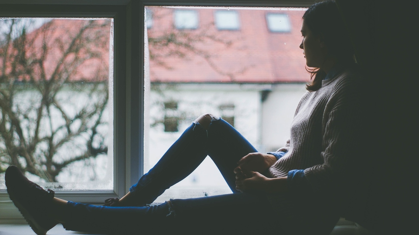 A young woman sits alone by a window, peering outside.