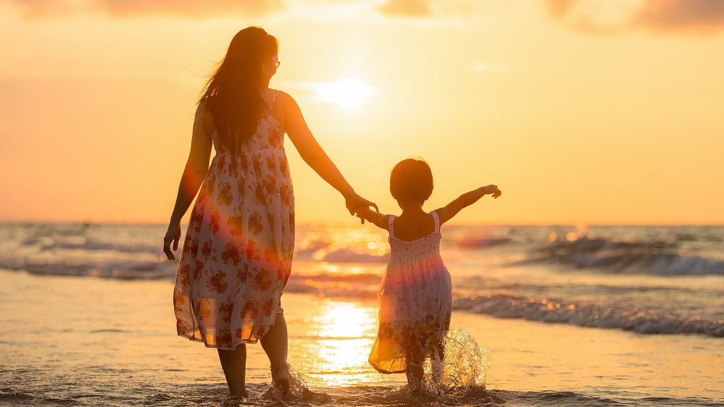 A mother and daughter walking on the beach.