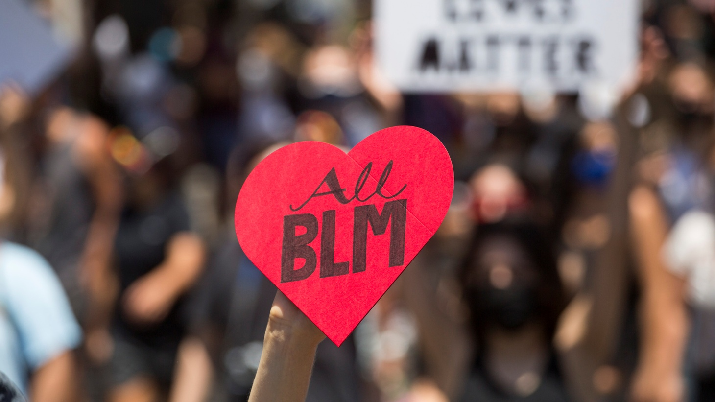 "A participant holding a heart shape sign reading ""All BLM"" takes part in an All Black Lives Matter march, organized by Black LGBTQ+ leaders in Hollywood, June 14, 2020."