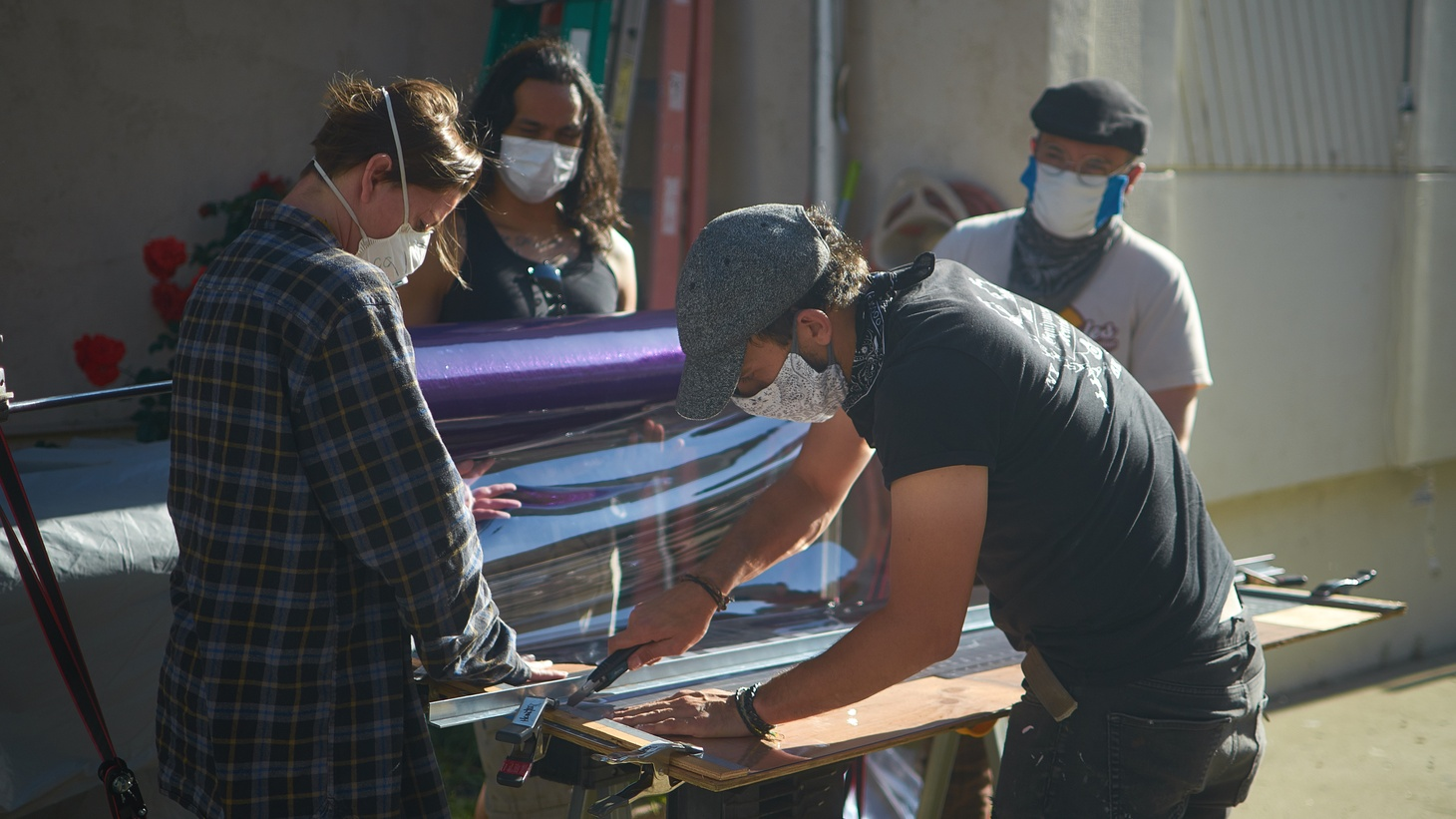 Prop maker Rob West (far right background) and fellow volunteers make protective face shields.