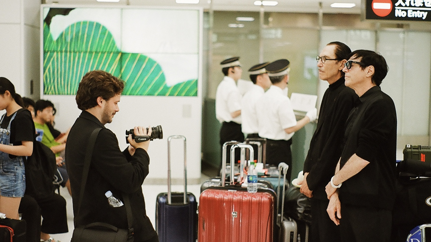 """Director Edgar Wright filming Ron Mael and Russell Mael in a Japanese airport from their film """"The Sparks Brothers."""""""
