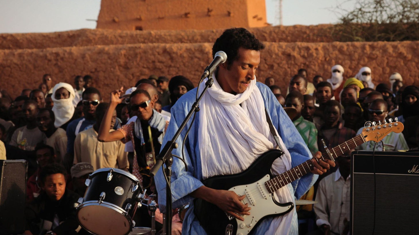 "Bombino is a young Tuareg singer and a guitar wizard whose riffs echo Jimi Hendrix and John Lee Hooker. Driven into exile from Niger, Bombino picked up his first guitar at age 12 and helps transport the traditions of his nomadic people into the future. Today's Top Tune is ""Tar Hani"" (My Love), from his CD, Agadez."