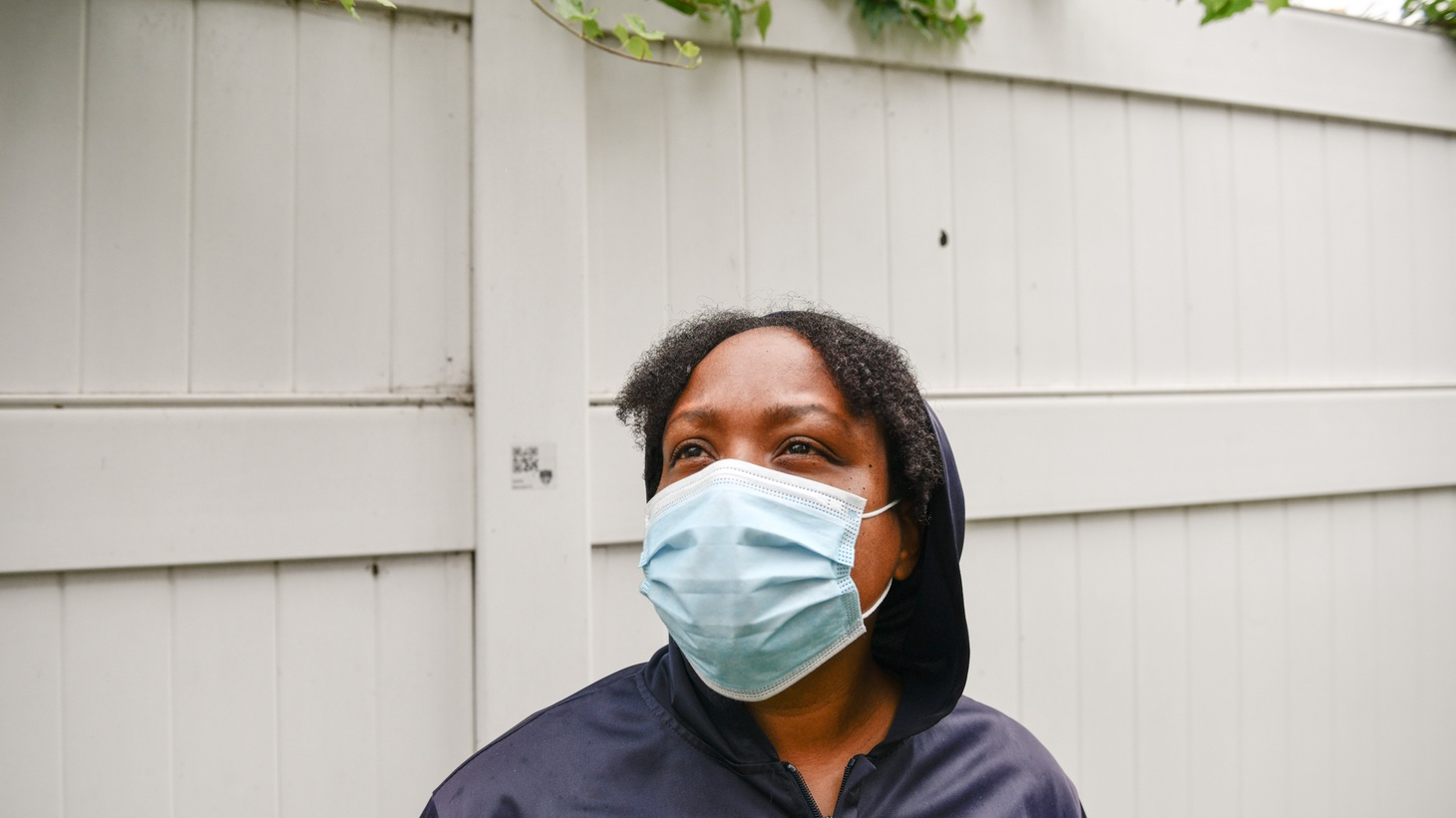 Rasheena McCord stands outside the hotel in Long Beach where McCord and her kids are living, on July 26, 2021. According to McCord, she has had to sleep on park benches after getting evicted one year ago. Housing Long Beach has assisted McCord in finding temporary housing.