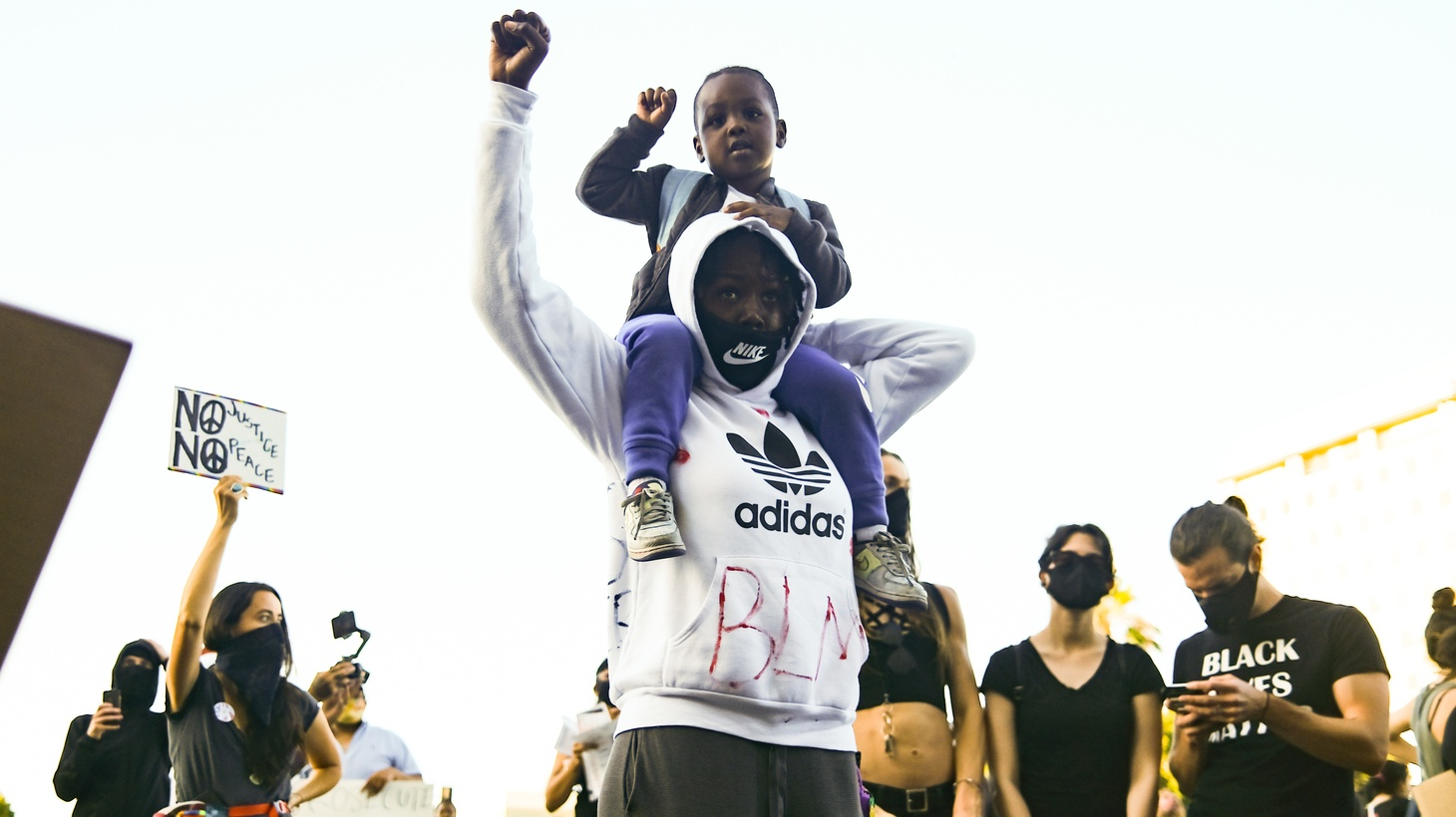 A demonstrator and their child raise their fists in the air in front of the federal prison in downtown LA during a rally.