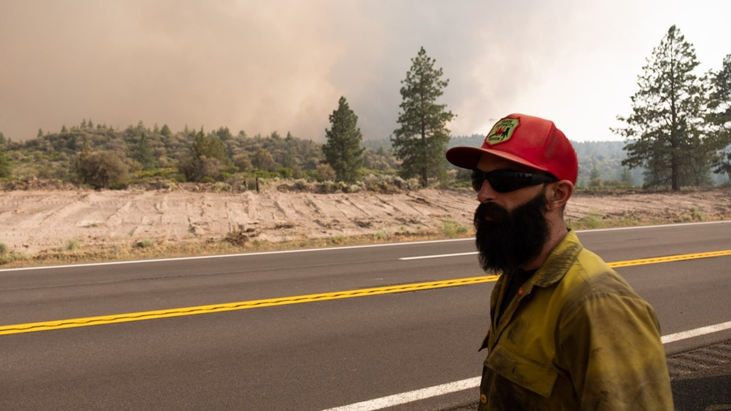 Firefighter Cody Hood watches the Lava Fire burn on a break Thursday, July 1, 2021. He has been deployed for his first-ever fire with Tahoe Hotshots, a federal firefighter crew and has been working for several days in difficult terrain.