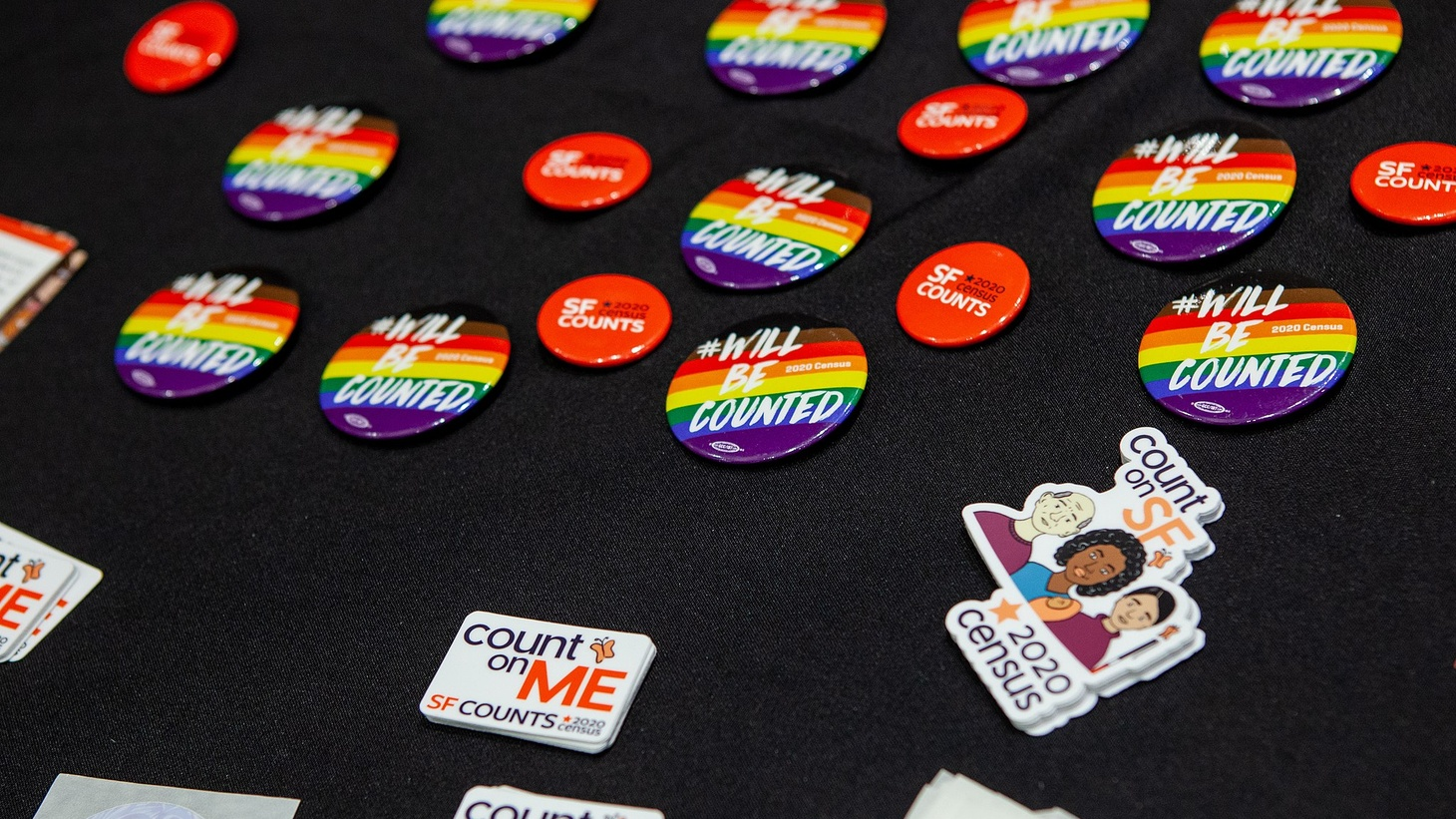 Buttons and stickers at an event for the 2020 Census and the LGBTQ community in San Francisco.
