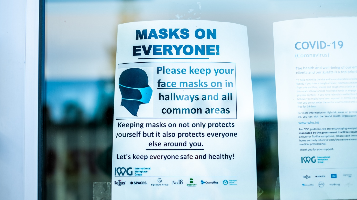A sign on the entrance door of a co-working office space in Culver City, California, says everyone must wear masks. July 28, 2020.