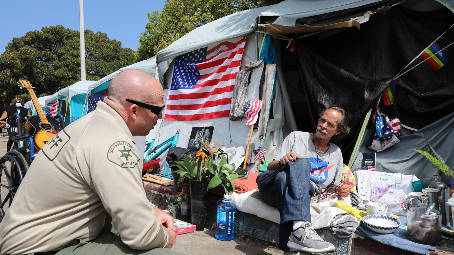 Douglas Bue, 65, speaks to a deputy with the LA County Sheriff's Department at the Veterans Row homeless encampment. Bue turned down an offer to go to the Dream Center but still hopes to move inside soon.