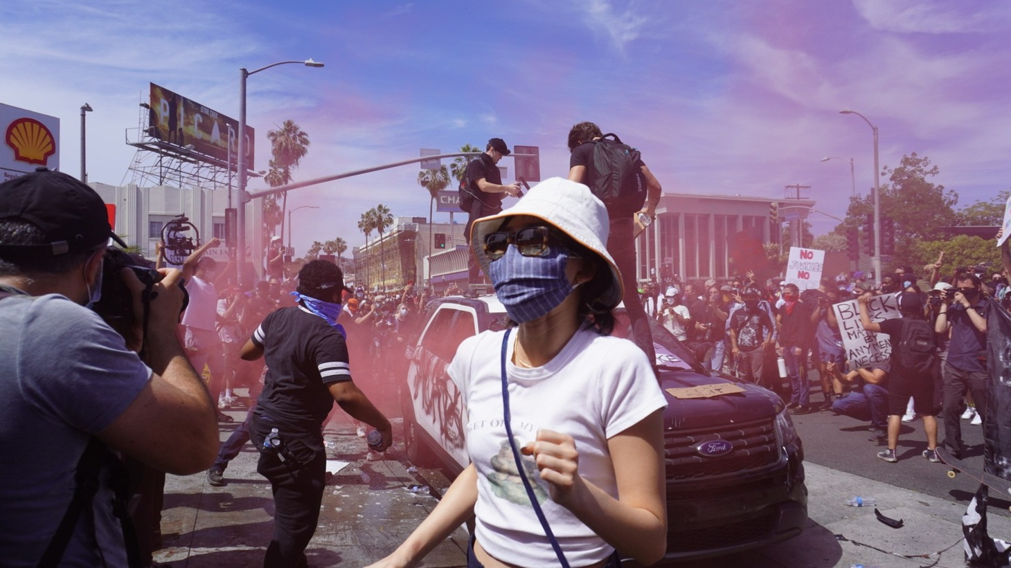 A woman gets out of the way as demonstrators smash a police car in the Fairfax district of Los Angeles.