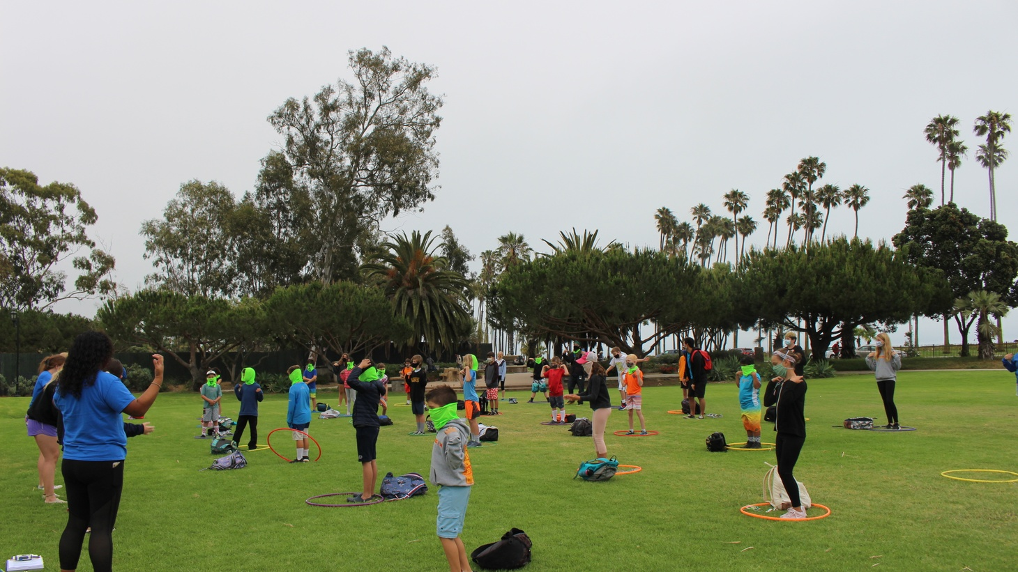 Kids at Nature Camp in Santa Barbara must stay inside a hula hoop, spaced six feet apart, during the morning sing-along.