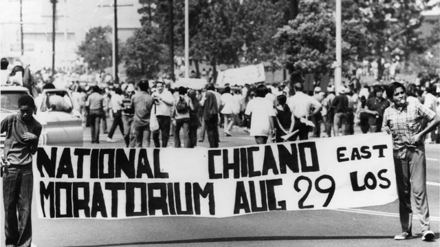 "Two young men hold a banner that says, ""National Chicano Moratorium, East Los Angeles, August 29."""