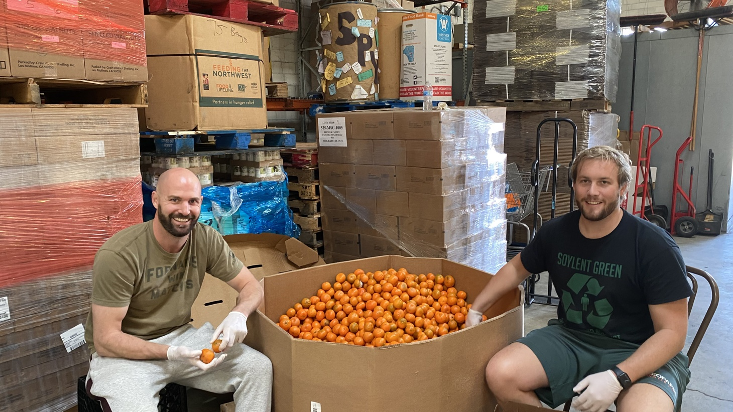 Ian Snook (left) and Viken Huening (right) working at a food bank before masks were being used.