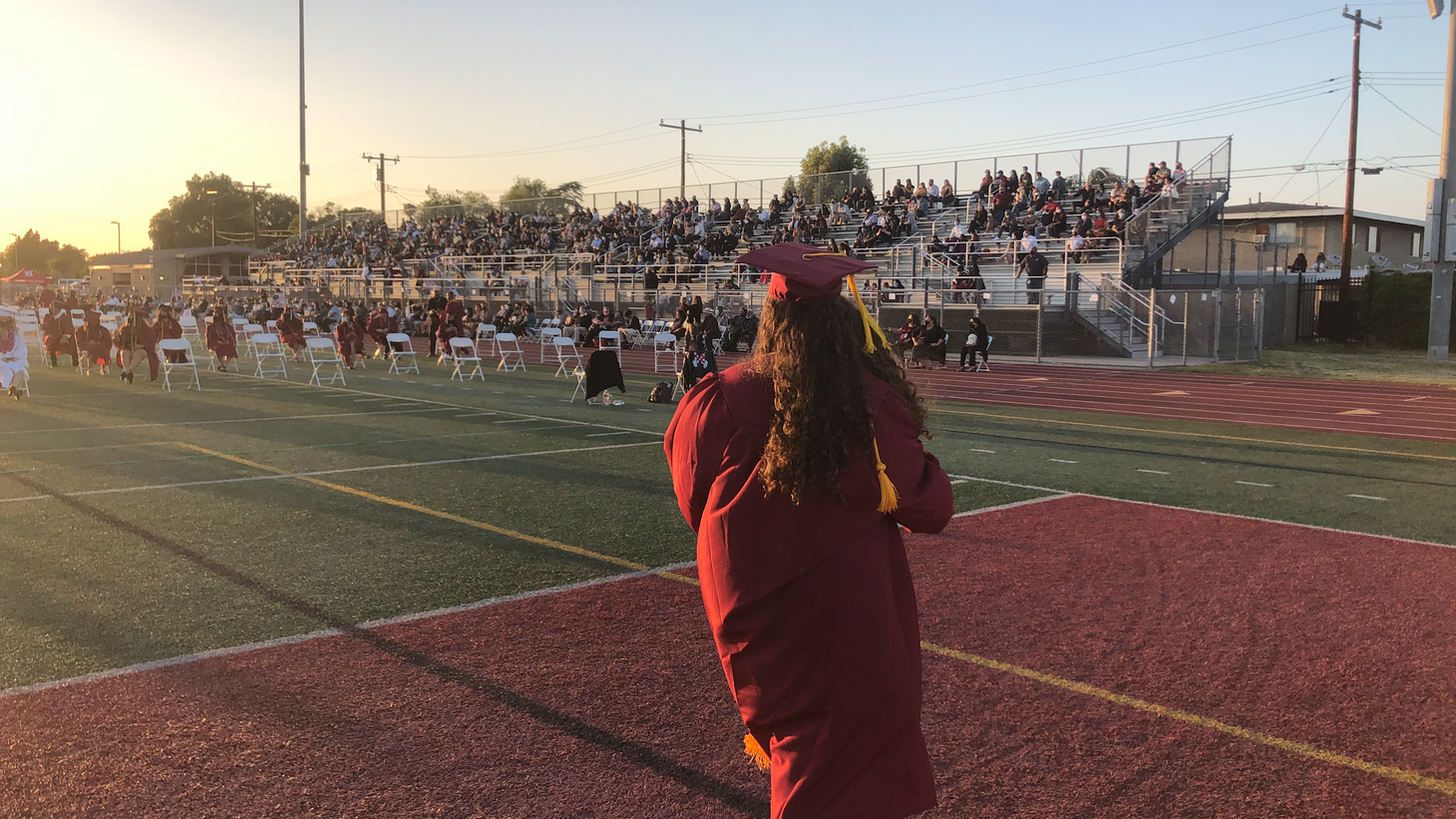A 2020 graduate walks across the stage, 12 months after receiving her high school diploma.