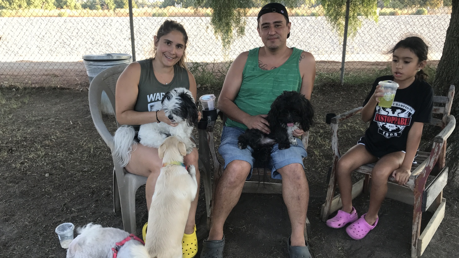 Natalia Ospina (left), her fiancé Dennis, and her daughter Scarlett hang out at the Sepulveda Basin Off-Leash Dog Park in Encino as their two dogs roam free. Photo by Benjamin Gottlieb.