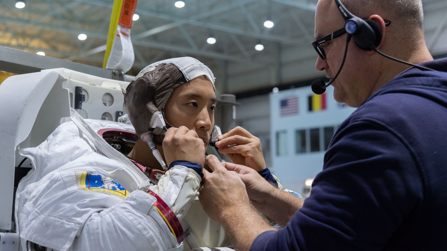 Jonny Kim is helped into a spacesuit prior to underwater spacewalk training at NASA Johnson Space Center's Neutral Buoyancy Laboratory in Houston.