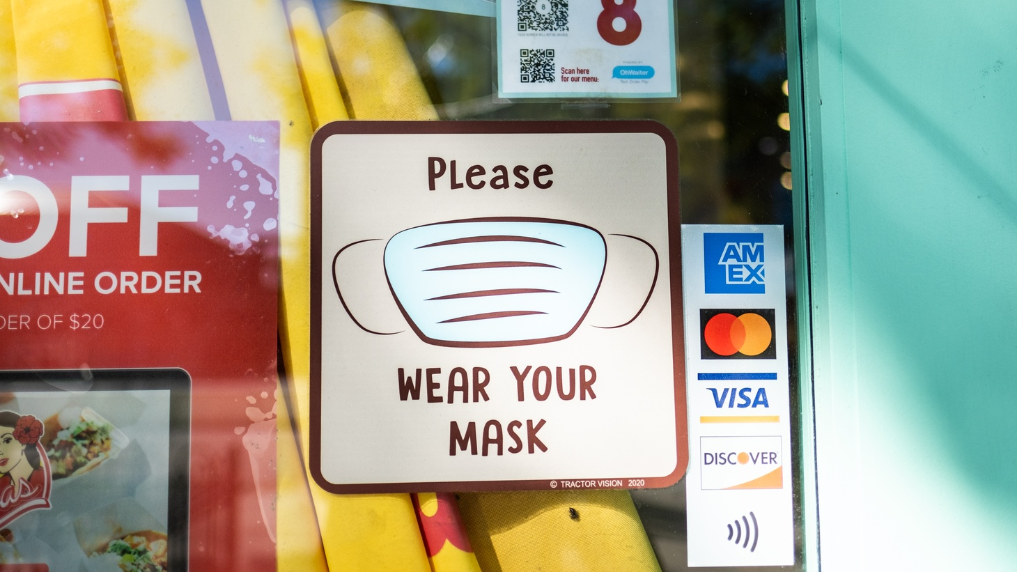 An entrance door sign at a business in Culver City reminds customers to wear their masks, January 21, 2021.