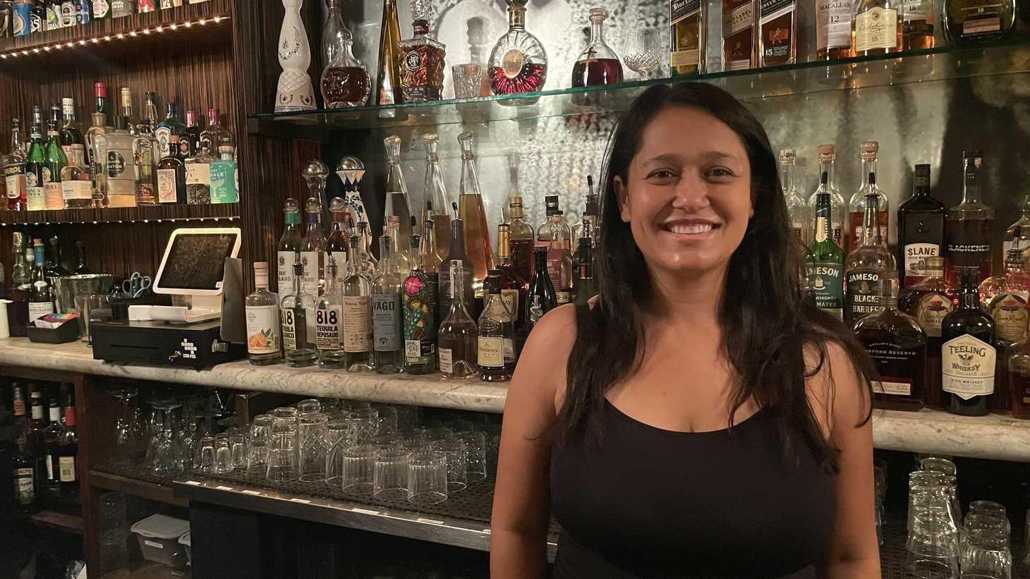 Camila Perry, owner of The North End Hollywood, stands behind her bar as she prepares to open for the evening. She's among the hundreds of small business owners who will be required to enforce a vaccine mandate starting next week.