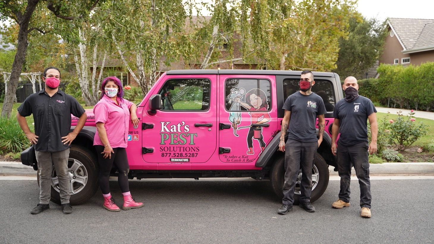 Kat Herrera, owner of Kat's Pest Solutions, stands in front of a hot pink company Jeep alongside her team of professional exterminators.