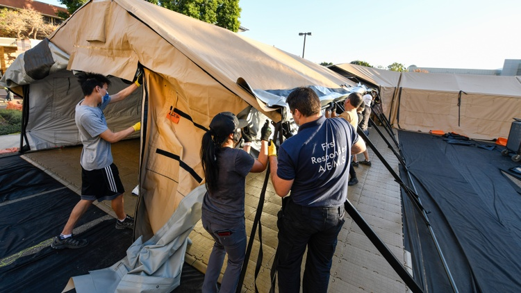 Strained hospitals in Orange County are putting up field tents to deal with the surge of COVID-19 patients.